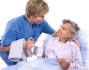 nurse helps the senior woman in washing